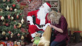 Girl steals a gift from Santa`s bag. Beautiful girl steals a gift from Santa`s bag stock video