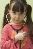 Girl with stethoscope. Girl have fun with stethoscope royalty free stock image