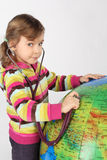 Girl with stethoscope and big inflatable globe Royalty Free Stock Images