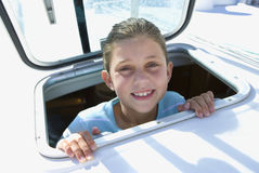 Girl (8-10) sticking head through open sailing boat cabin window, smiling, close-up, portrait Royalty Free Stock Photo
