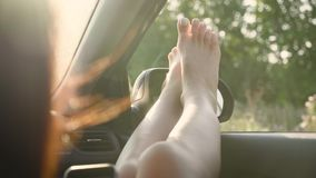 A girl by sticking out her legs in an open window car. Young woman likes to travel by car, travel concept, lifestyle. stock footage