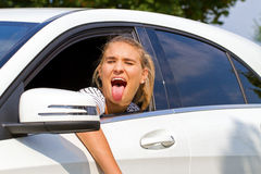 Girl sticking tongue out. Girl in a car sticking tongue out Stock Photo