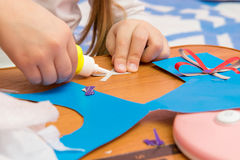 Girl sticks two strips, making crafts out colored paper Royalty Free Stock Photo