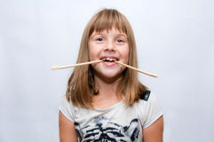Girl and sticks. Young girl and chinese sticks in mouth - fun pose Royalty Free Stock Photo
