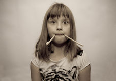 Girl and sticks. Young girl and chinese sticks in mouth - old filter Royalty Free Stock Photo