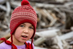 Girl in stocking cap beach combing. Girl with red/white stocking cap, freckles, on wood covered beach Stock Images