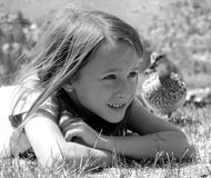Girl on stomach with duck. Little girl on stomach with duck ducks ,  by June Lake Stock Photography