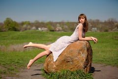 The girl on a stone. The girl in a dress lies on a stone the barefooted Stock Image