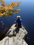 Girl on the stone ashore. Girl on fall day ashore of Island pond stock photo