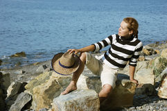 Girl on a stone beach with a hat in a hand Stock Images
