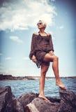 Girl on stone coast near sea Royalty Free Stock Photography