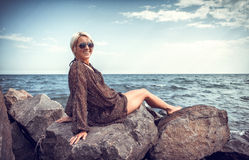 Girl on stone coast near sea Stock Image