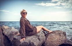 Girl on stone coast near sea Stock Image