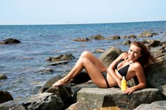 Girl on a stone with a cream for sunburns Royalty Free Stock Image