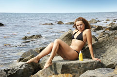 Girl on a stone with a cream for sunburns Stock Photo