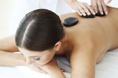 Girl on stone therapy. Girl on a stone therapy, hot stone massage Royalty Free Stock Photos