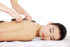 Girl on a stone therapy, hot stone massage.  Royalty Free Stock Image