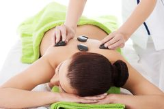 Girl on a stone therapy, hot stone massage Stock Photos