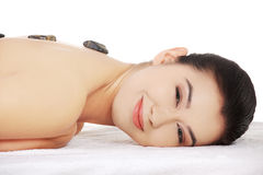 Girl on a stone therapy, hot stone massage Stock Photography