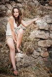 Girl on the stone wall background Stock Photo