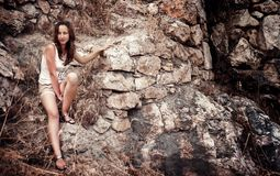 Girl on the stone wall background Royalty Free Stock Image