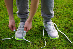 Girl stopped running to tie the laces on shoes. Stock Photos