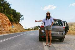 The girl stops the car on the roadway stock photography