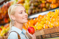 Girl at the store choosing fruits hands apple Royalty Free Stock Photo