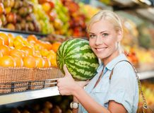 Girl at the store choosing fruits hands watermelon Royalty Free Stock Photo