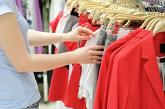 The girl in the store is looking at the clothes. royalty free stock photography