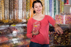 Girl in store is picking up candies Royalty Free Stock Images