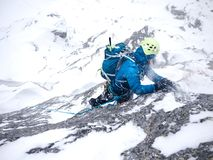 Girl in the storm during an extreme winter climb. West italian A Royalty Free Stock Image
