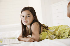 Girl With Story Book In Bed. Portrait of little girl with story book in bed Royalty Free Stock Photo