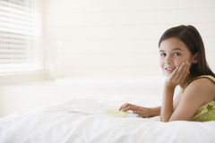 Girl With Story Book In Bed. Portrait of relaxed little girl with story book in bed Royalty Free Stock Photography