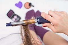 Girl straightening her hair in bed Royalty Free Stock Images
