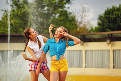 Girl straightens hairstyle best friend. Teen girl straightens hairstyle's best friend at the fountain in summer park. Girls dressed in shorts and a shirt Stock Image