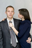 The girl straightens his tie man. Woman hugging a man and carefully adjusts his tie Stock Photo
