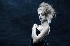 Girl with strange hair. Girl with original make-up posing - blue tone royalty free stock image