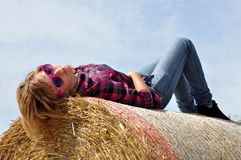 The girl on the straw bale. The girl  lying on the straw bale in background blue sky Stock Photography