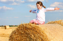 Girl on the straw after harvest field. Small rural girl on the straw after harvest field with straw bales Stock Photos