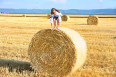 Girl on the straw after harvest field with straw bal Stock Photo