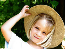 Girl with straw hat. 6 year old girl with straw hat under a tree Royalty Free Stock Images