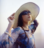 Girl in straw hat. Beautiful girl wearing straw hat and sunglasses on the beach. Film scan, middle format Royalty Free Stock Photo