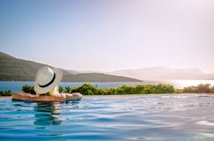 A girl in a hat admires the sunset from the pool. royalty free stock image