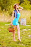 Girl in a straw hat with a basket of spring flowers and the outdoors Royalty Free Stock Images
