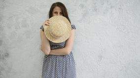 Girl and a straw hat. Beautiful young positive girl in a straw hat near a gray wall stock video footage