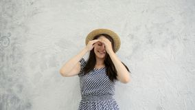 Girl and a straw hat. Beautiful young positive girl in a straw hat near a gray wall stock footage