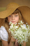 Girl in a straw hat with a bouquet of flowers Stock Photo