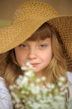 Girl in a straw hat with a bouquet of flowers Stock Image