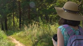 A girl in straw hat and dress walks through the park and photographs nature stock video